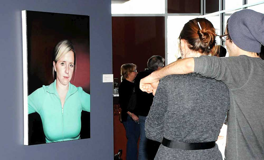 A woman and a man standing close together while viewing a portrait at the exhibition