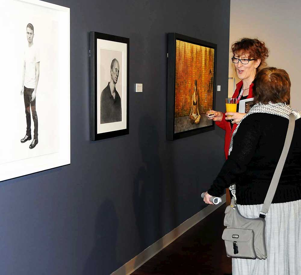 Two women discussing a portrait from the exhibition