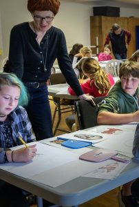 Art teacher overseeing work by students